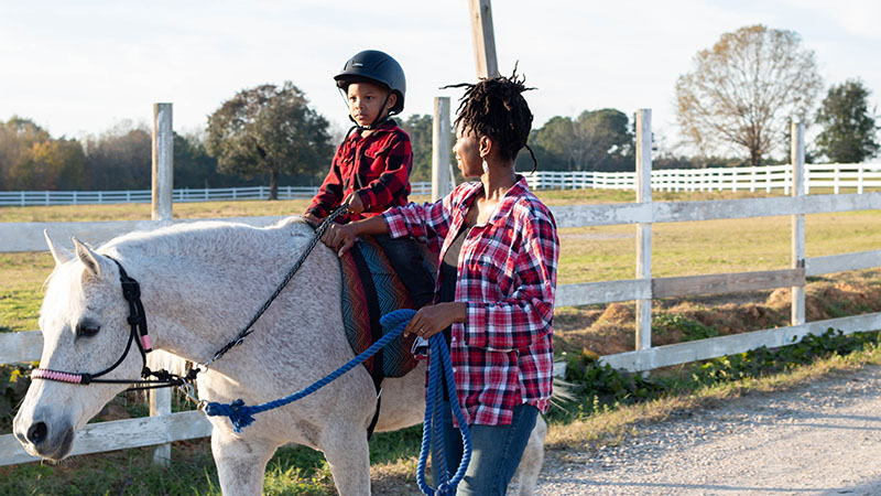 Caitlin Gooch, pictured teaching student Sevyn, founded Saddle Up and Read in 2017, and it became a 501(c)(3) in 2019. Brandi Alexis photo.